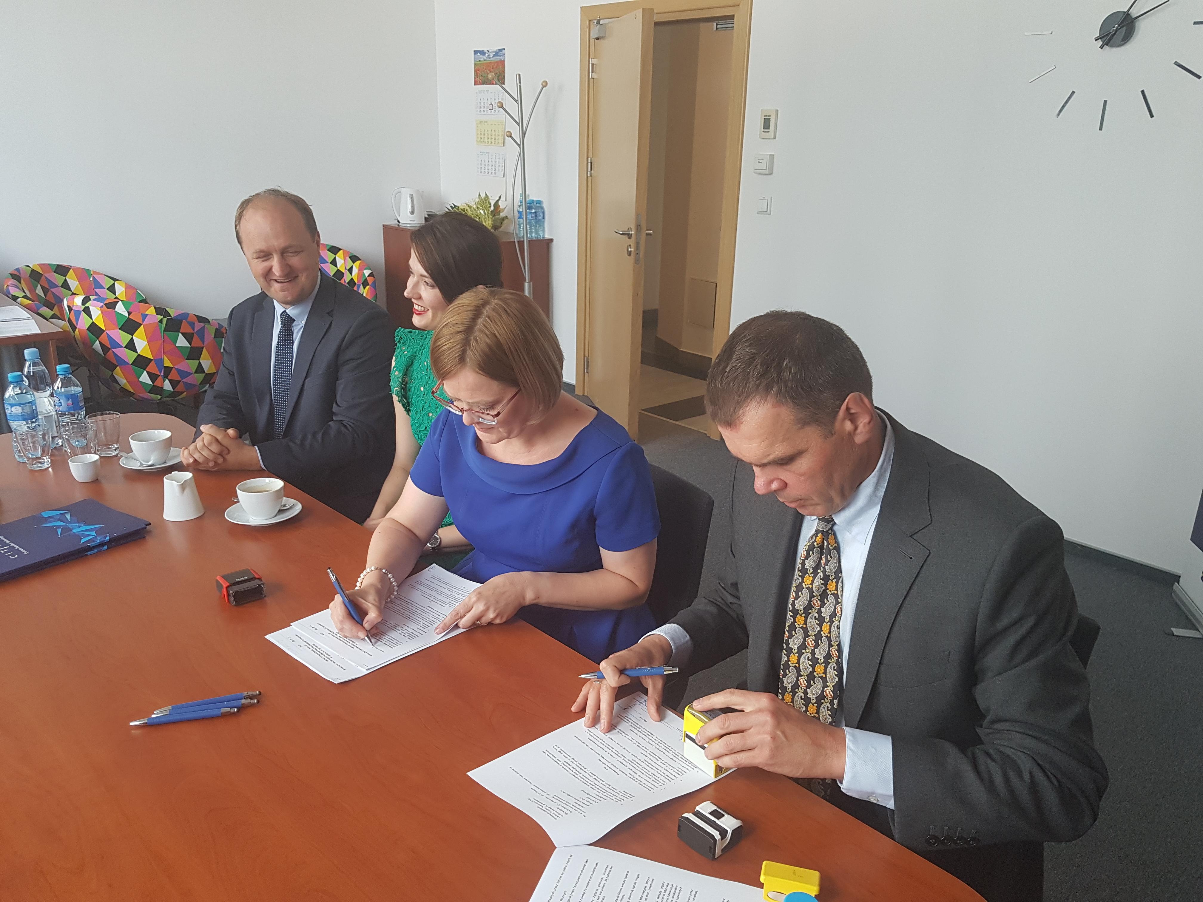 Cztery osoby siedzą przy stole, dwie z nich podpisują dokumenty