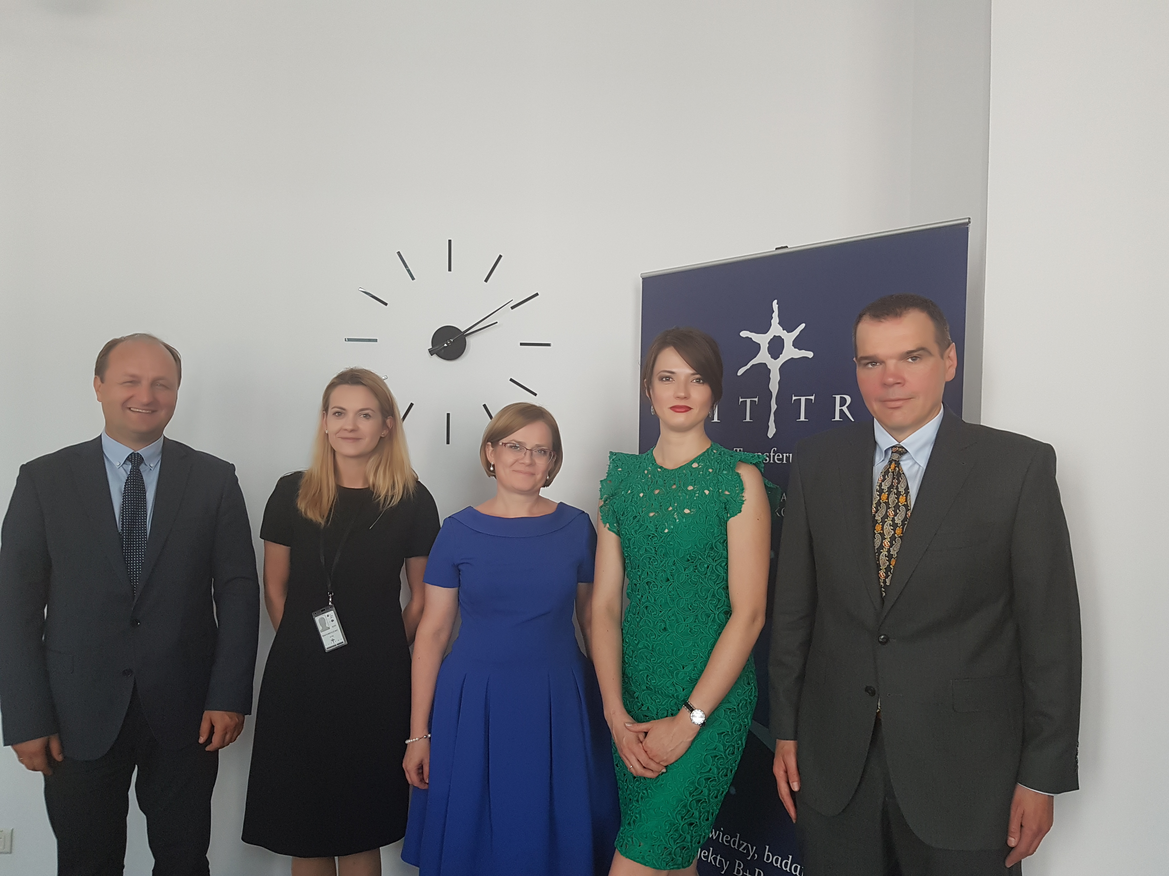 Pięć osób ubranych elegancko stoi uśmiechnięte. W tle widać zegar i logo CITTRU.