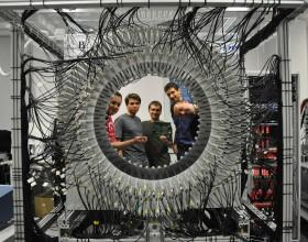 Czterech mężczyzn zaglądających do wnętrza urządzenia