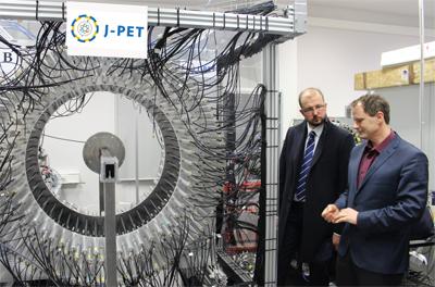 Profesor Moskal i Piotr Dardziński stojący obok wynalazku J-PET